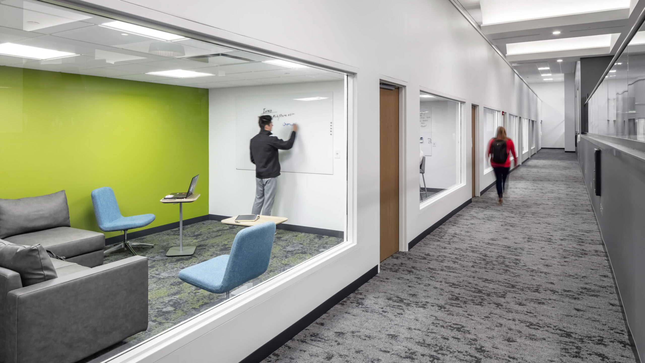 Glass-enclosed study room with a bright green accent wall.