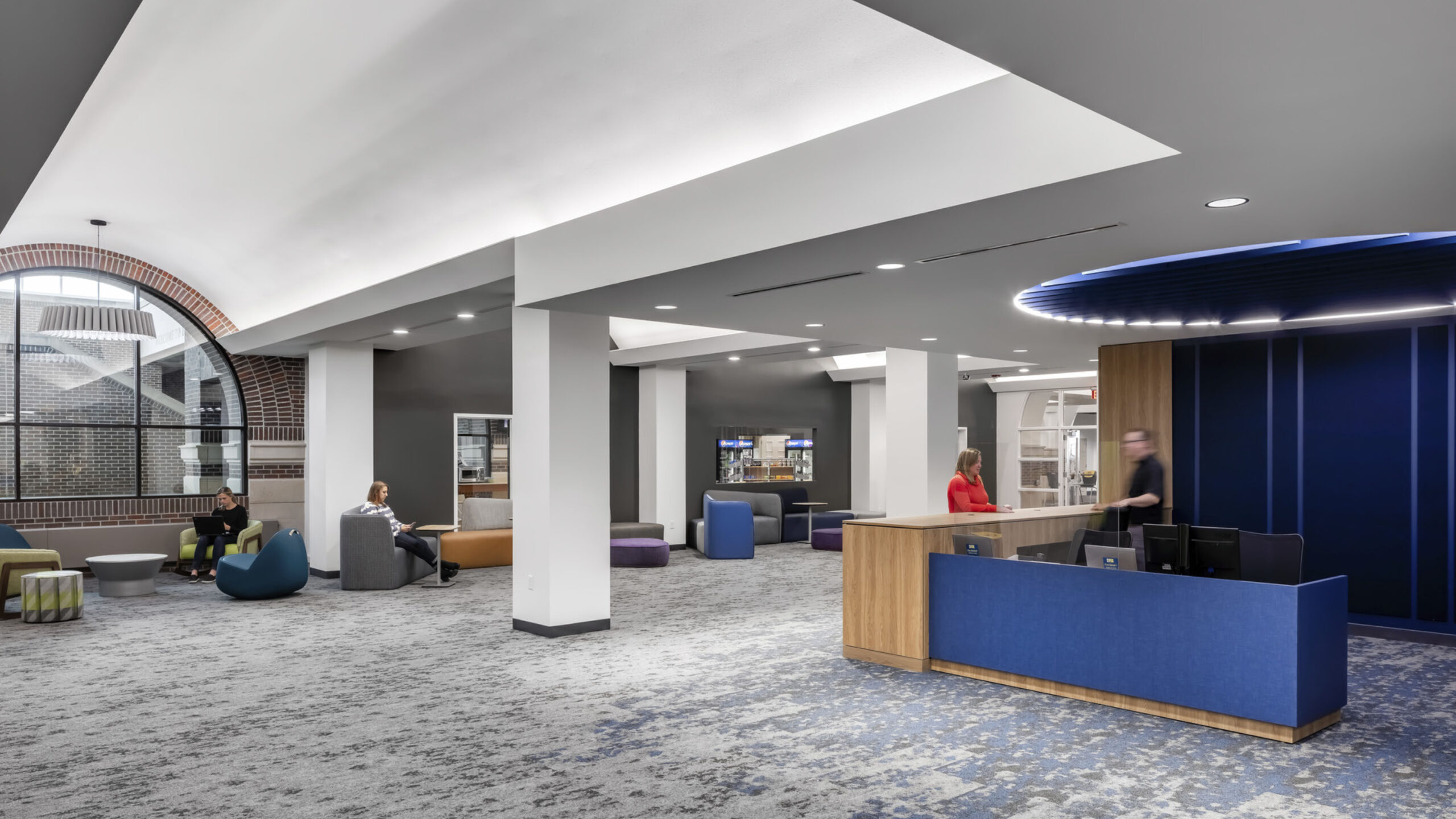 A library welcome desk with blue wayfinding elements.