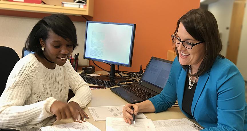 Stefnee Trzpuc and a design research student intern discuss a collaborative research paper.