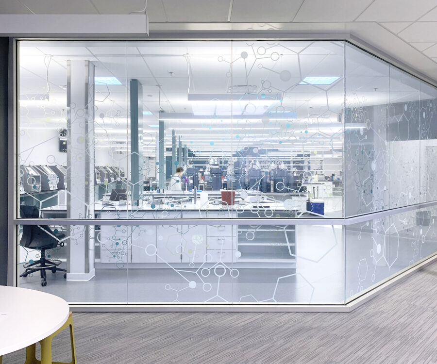 A corridor view into a quality control lab with a graphic design glass pattern.