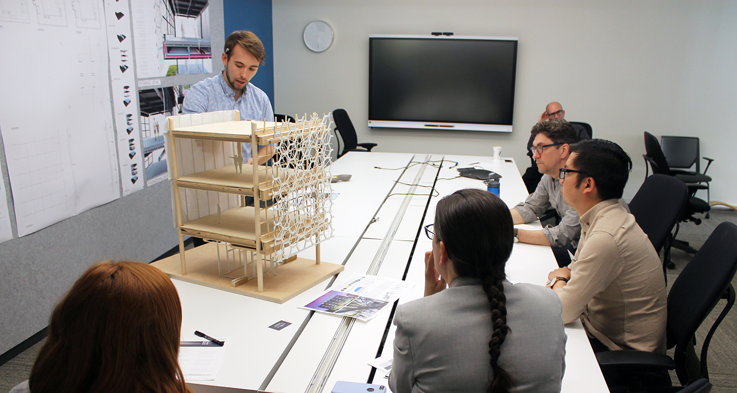 A student presents an architectural model to a group of BWBR employees during the BWBR Prize competition.